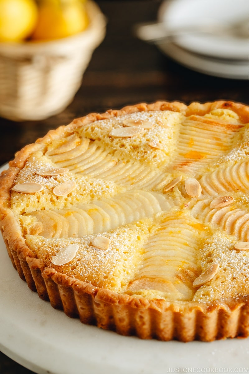 Pear and Almond Tart (Pear Frangipane Tart) dusted with powdered sugar and sprinkled with toasted almond slices.
