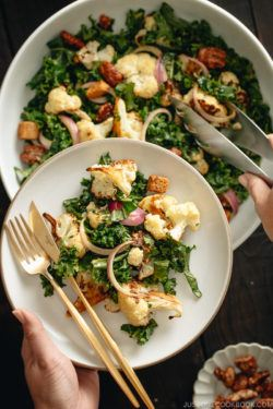 A large white bowl containing Roasted Cauliflower Kale Salad tossed with Miso Tahini Dressing.