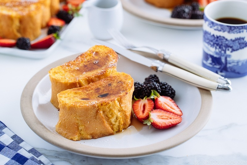 A plate containing French toast, strawberries, and black berries.