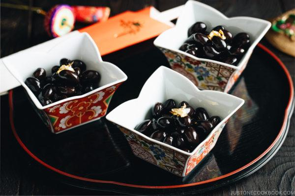 Sweet black soybeans garnished with a gold leaf in Japanese red and gold dishes.