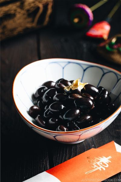 Sweet black soybeans garnished with a gold leaf in a Japanese blue and white bowl.