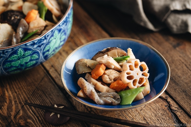 A blue Japanese bowl containing Nishime, simmered vegetables and chicken.