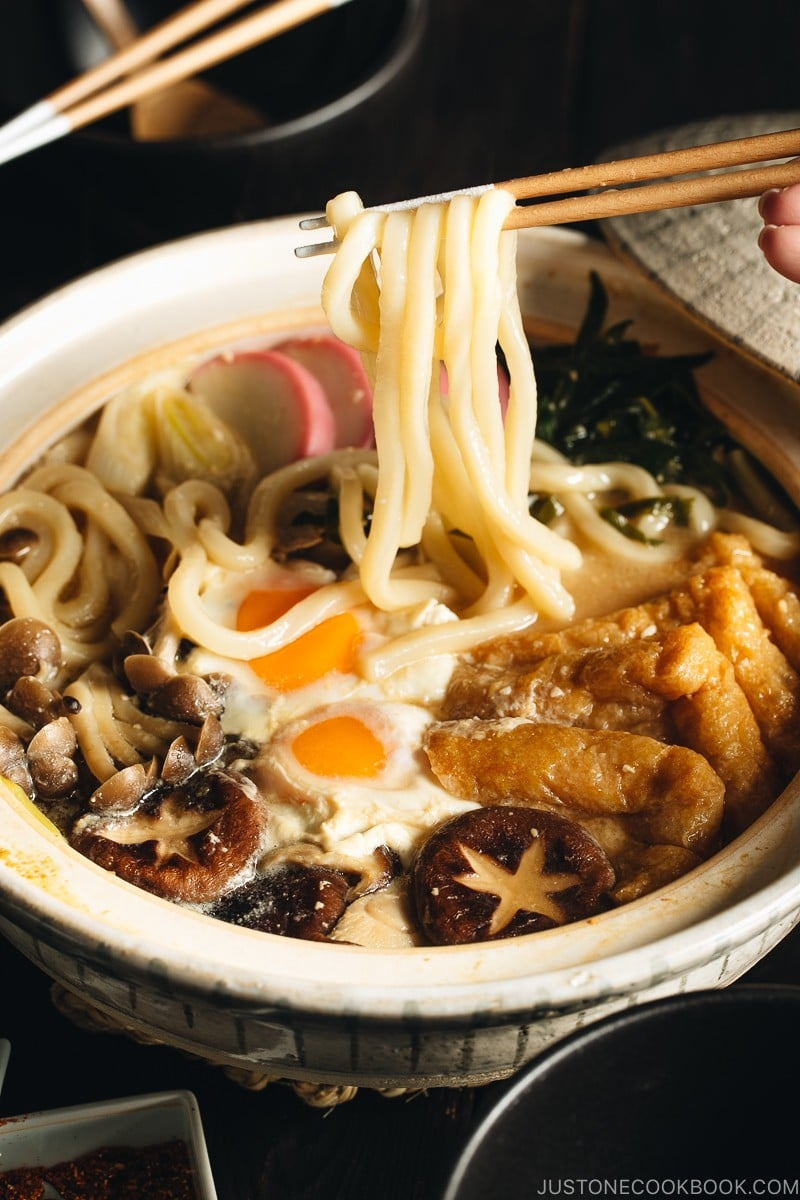 A donabe containing udon noodles, chicken, fish cakes, deep fried tofu, mushrooms, and leeks in a hearty miso broth.