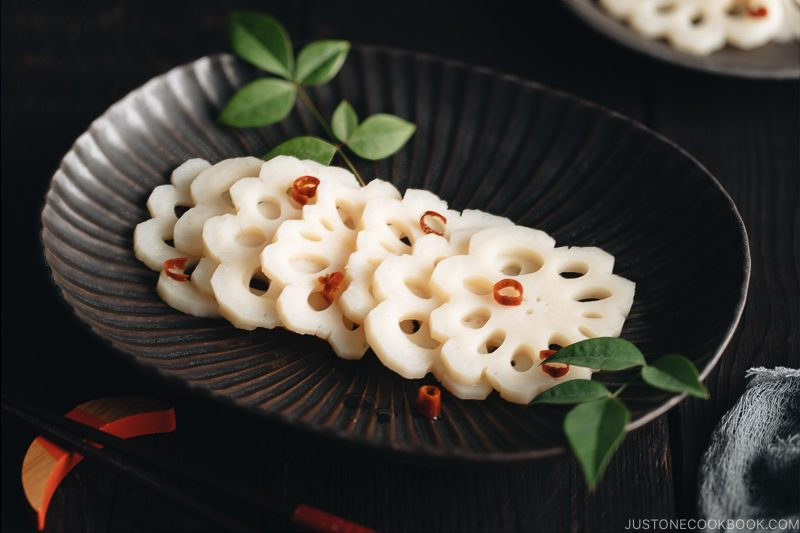 A black plate containing Pickled Lotus Root (Su Renkon), garnished with chopped red chili pepper.