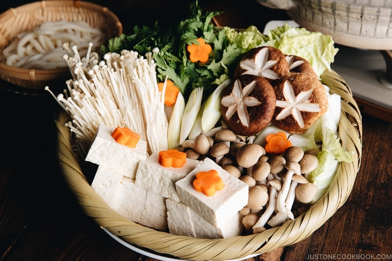 Assorted vegetables, tofu, and mushrooms in a bamboo basket, ready to cook in Shabu Shabu.