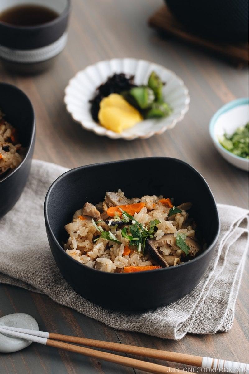 Black ceramic bowls containing Japanese Mixed Rice (Takikomi Gohan).