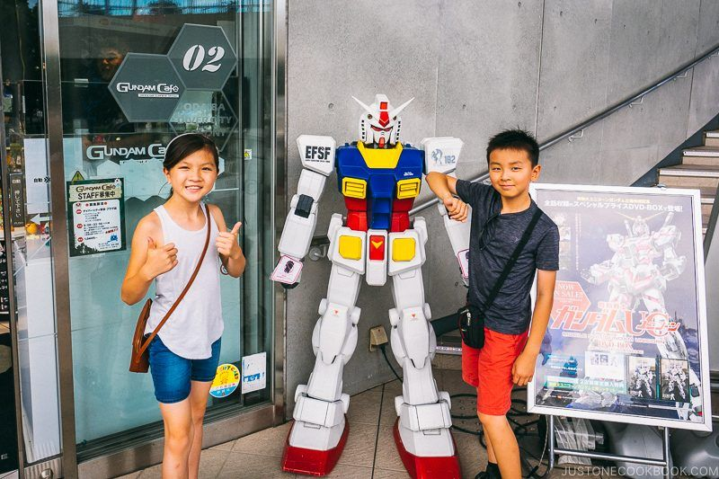 children next to small Gundam Statue at Gundam Cafe - Tokyo Odaiba Travel Guide | www.justonecookbook.com