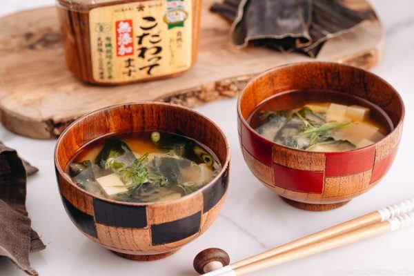 Japanese wooden bowls containing vegan miso soup with tofu and seaweed.