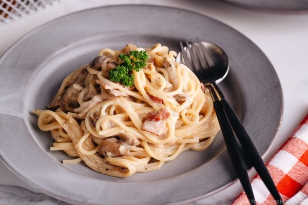 Creamy Mushroom and Bacon Pasta on a grey plate.
