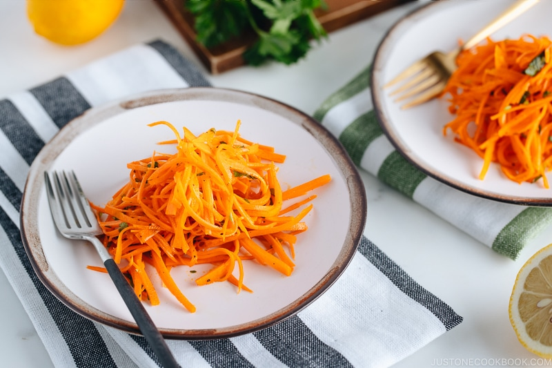 Carrot salad on a white plate with gray rim.