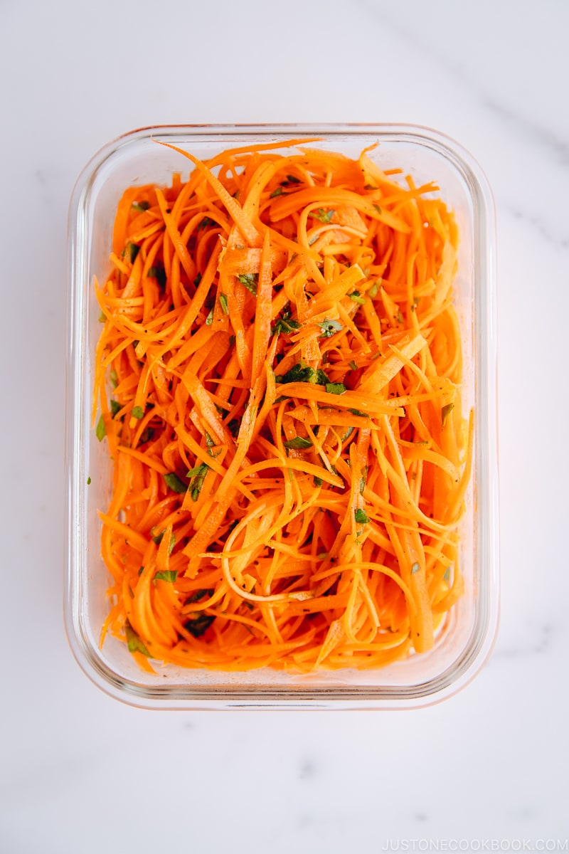 Carrot salad in a glass meal prep container.