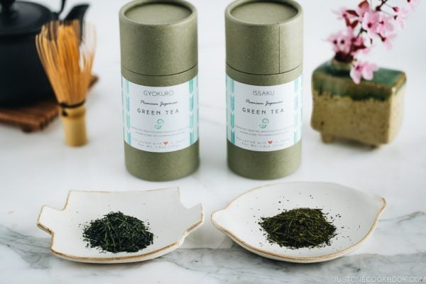 Two types of Japanese green tea and their containers along with tea pot.