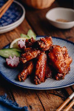 Orange teriyaki chicken wings on a blue patter.