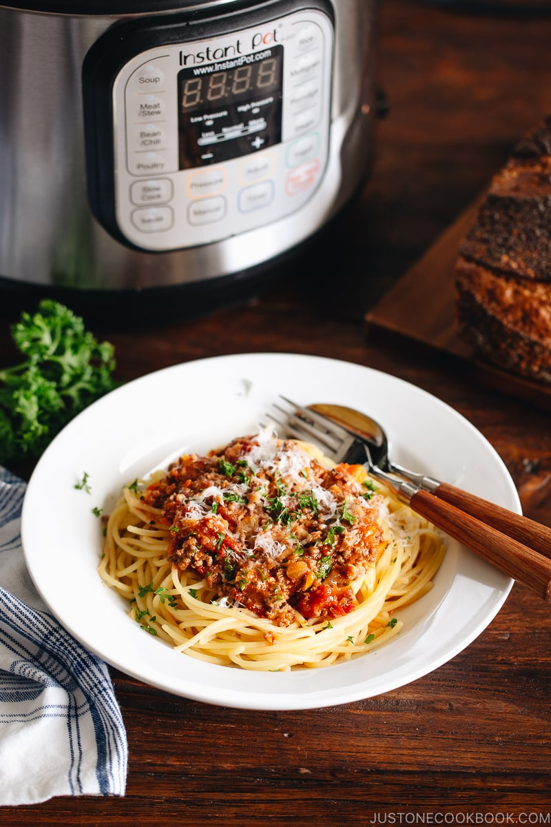 Spaghetti Bolognese on a white plate next to the Instant Pot.