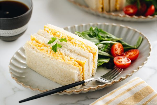 Tamago Sando - Japanese Egg Salad Sandwich on a plate along with salad.