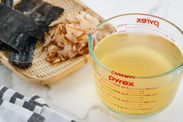 Awase Dashi in a measuring cup, and kombu and katsuobushi on a bamboo basket.