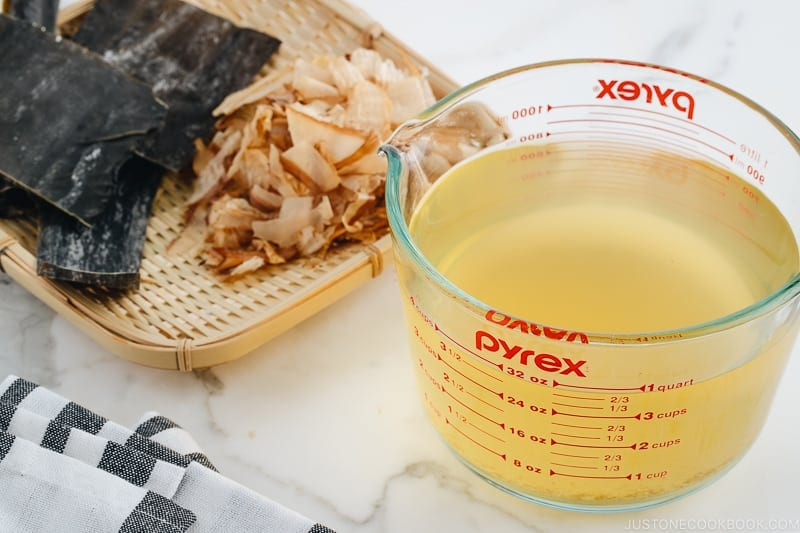 Awase Dashi in a measuring cup, and kombu and katsuobushi on a bamboo basket.