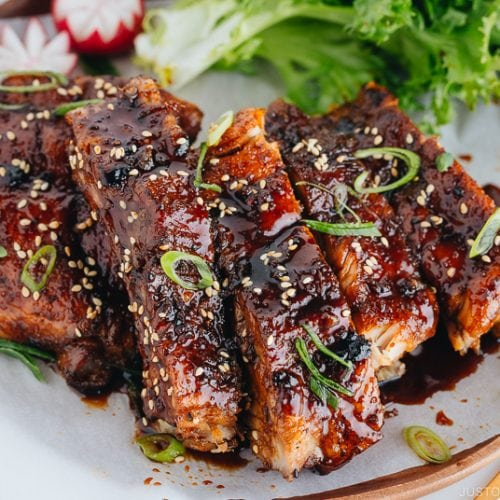 Sticky Asian Ribs on a white platter, topped with sprinkle of green onion.