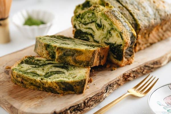 A few slices of matcha marble pound cake served on a wooden board.