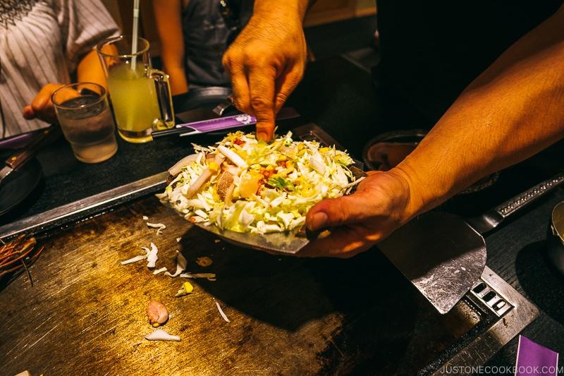 okonomiyaki mixture about to poured onto hot plate at Ajinoya - Osaka Guide: Dotonbori and Namba | www.justonecookbook.com