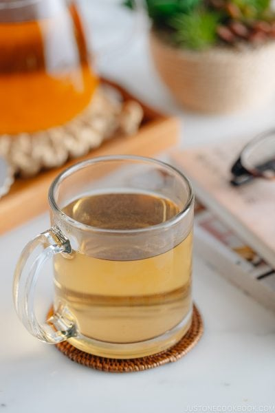 Hot buckwheat tea (sobacha) served in a glass cup.