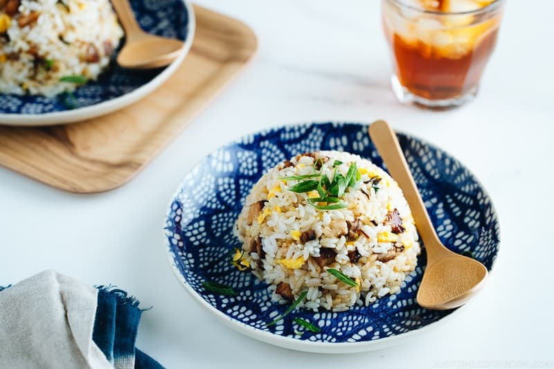 Chashu fried rice on the blue plate, garnish with chopped green onions.