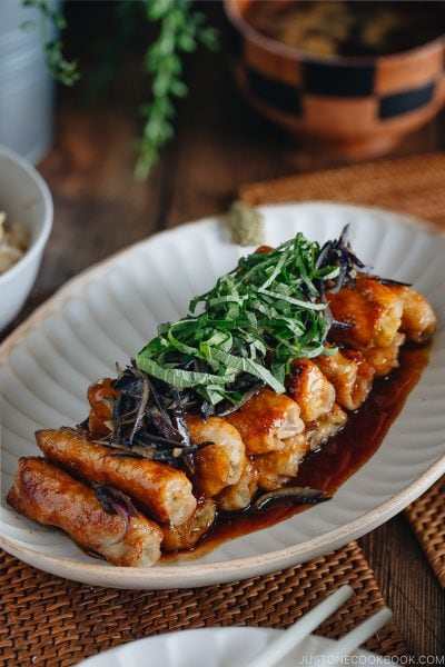 A Japanese white plate containing ginger pork rolls with eggplant garnished with shiso leaves on top.