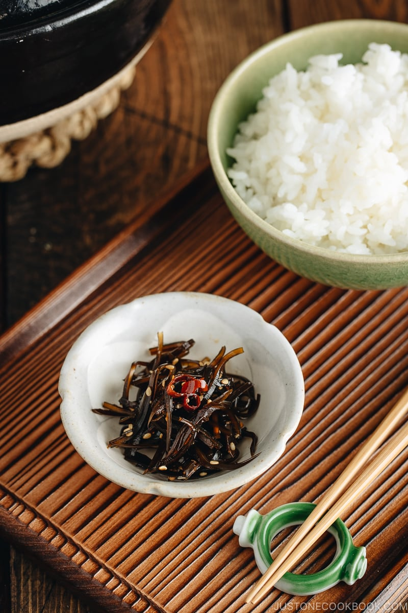 Simmered kombu in a small dish next to a bowl of steamed rice.