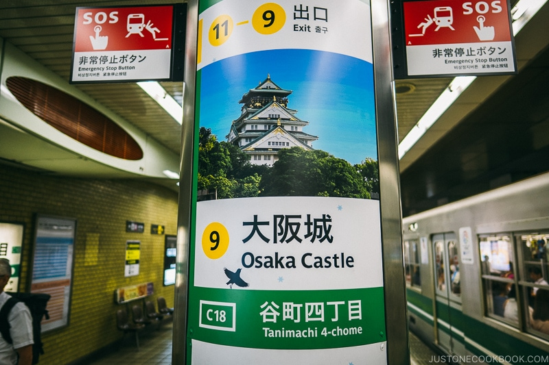 A sign for Osaka Castle on the side of a train station