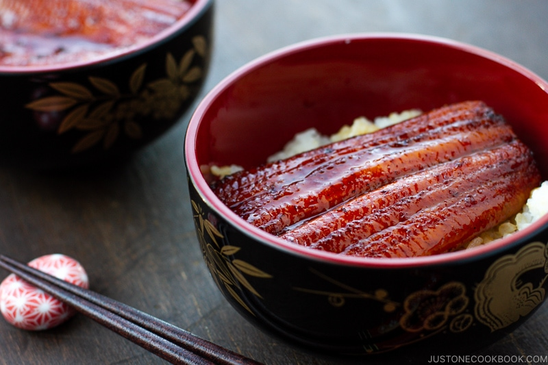 A lacquer bowl containing Unagi (Eel) over steamed rice.