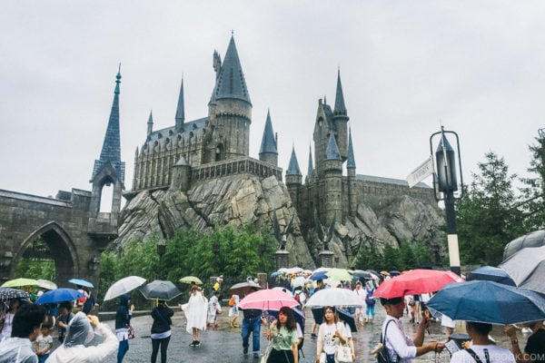 A group of people walking in the rain with an umbrella at Universal Studios Japan