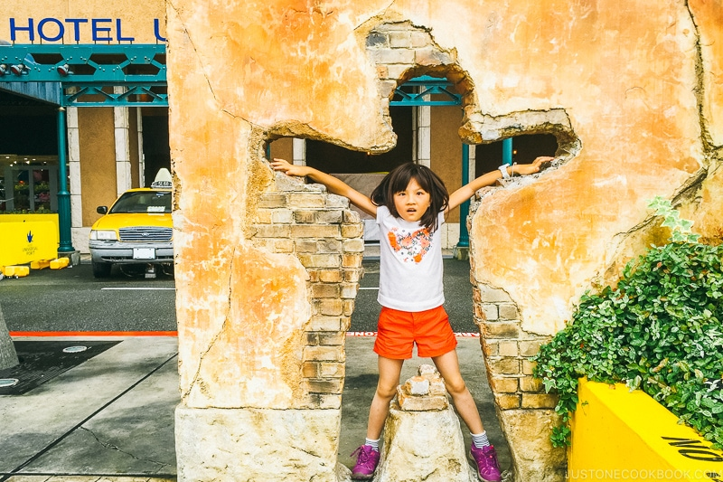 child posing inside a hole in a wall at Hotel Universal Port - Osaka Guide: Universal Studios Japan | www.justonecookbook.com
