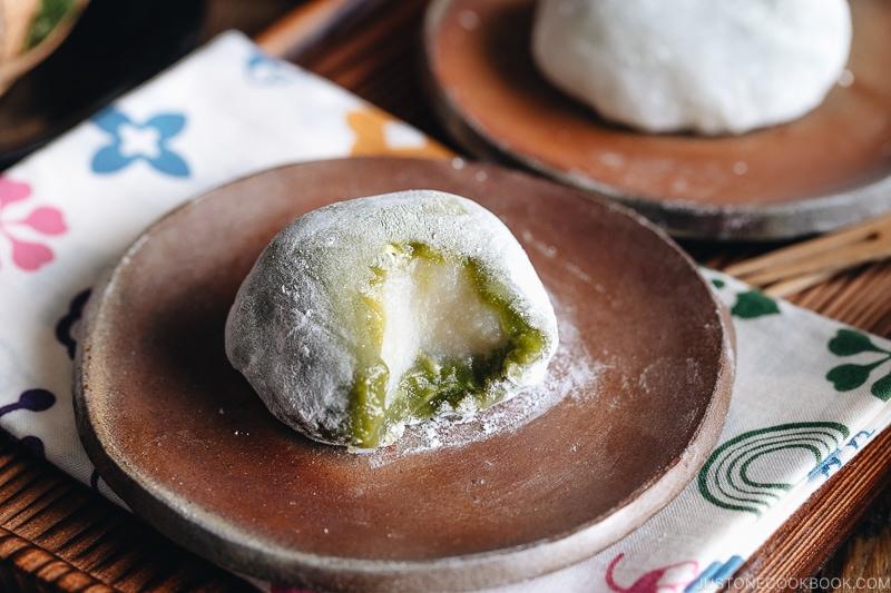 Green tea mochi showing inside white bean paste.
