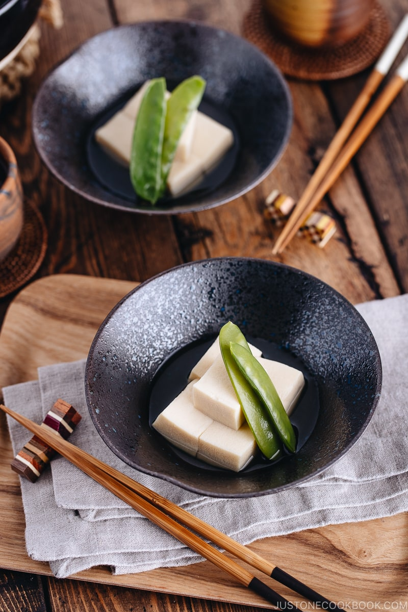 Simmered koyadofu with snow peas in a black ceramic bowl.