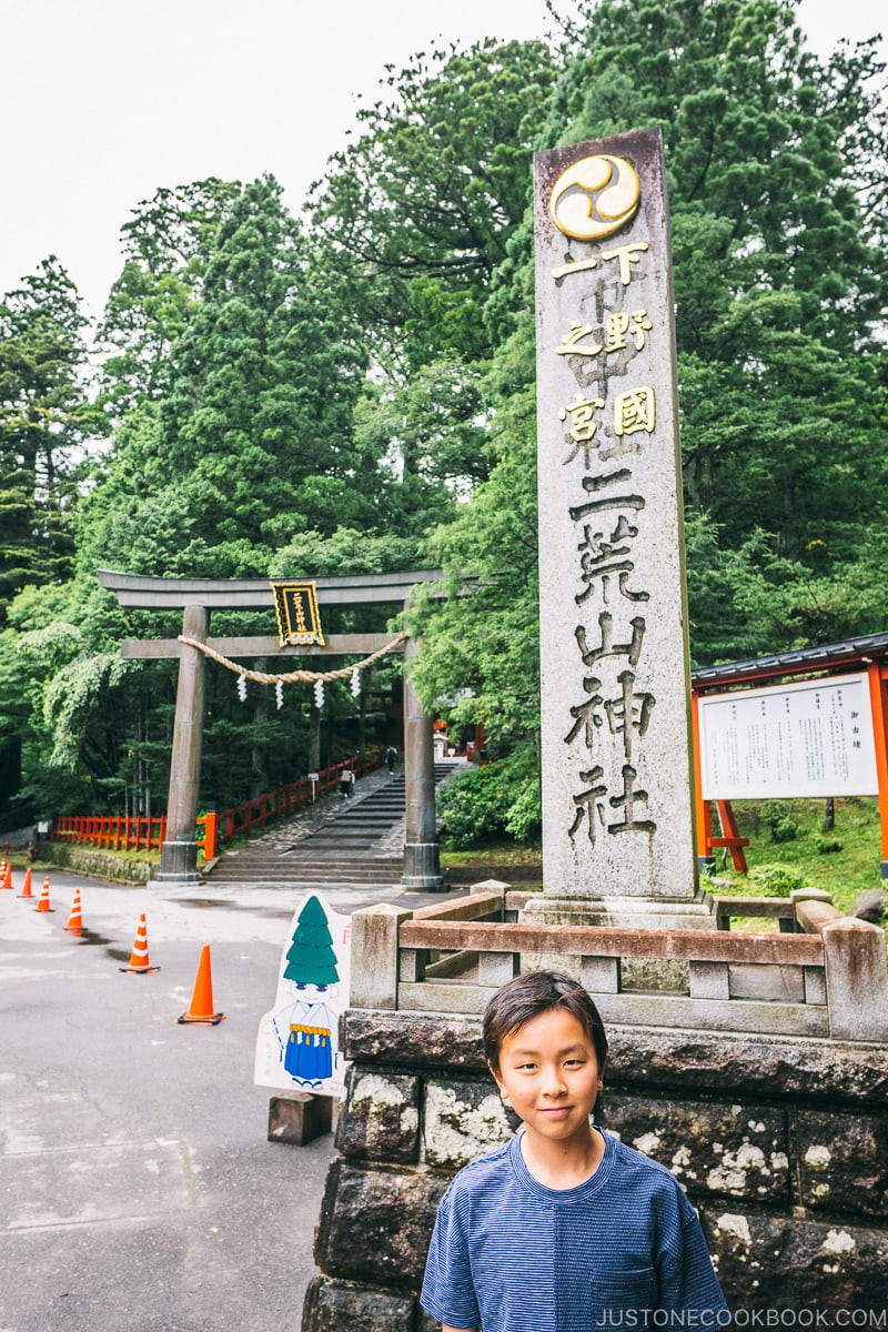 child standing in front of Nikko Futarasan Jinja stone monument - Places to Visit and Things to do in Nikko | www.justonecookbook.com
