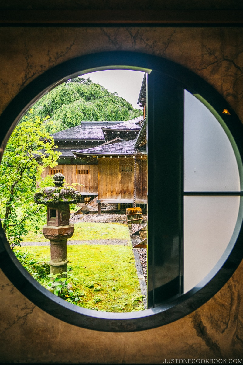looking through a circle window into the garden at Nikko Tamozawa Imperial Villa Memorial Park - Places to Visit and Things to do in Nikko | www.justonecookbook.com