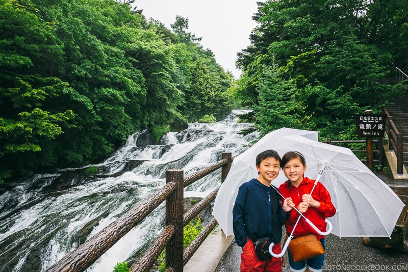 children with umbrella next to Ryuzu Falls - Things to do around Lake Chuzenji | www.justonecookbook.com
