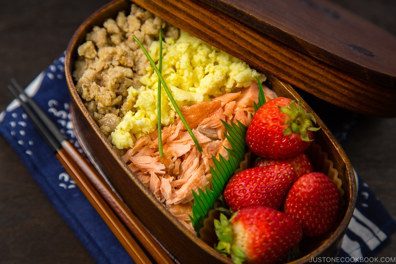 Ground chicken, egg, and salmon over rice in a wooden bento box.