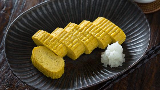 Tamagoyaki and grated daikon on a black plate.
