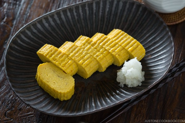 Tamagoyaki and grated daikon on a black plate.