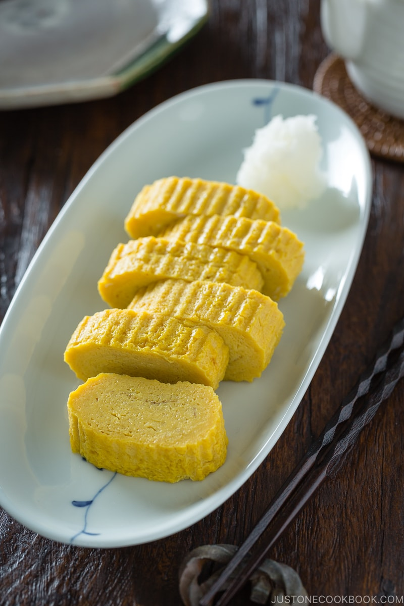 Tamagoyaki and grated daikon on a white plate.