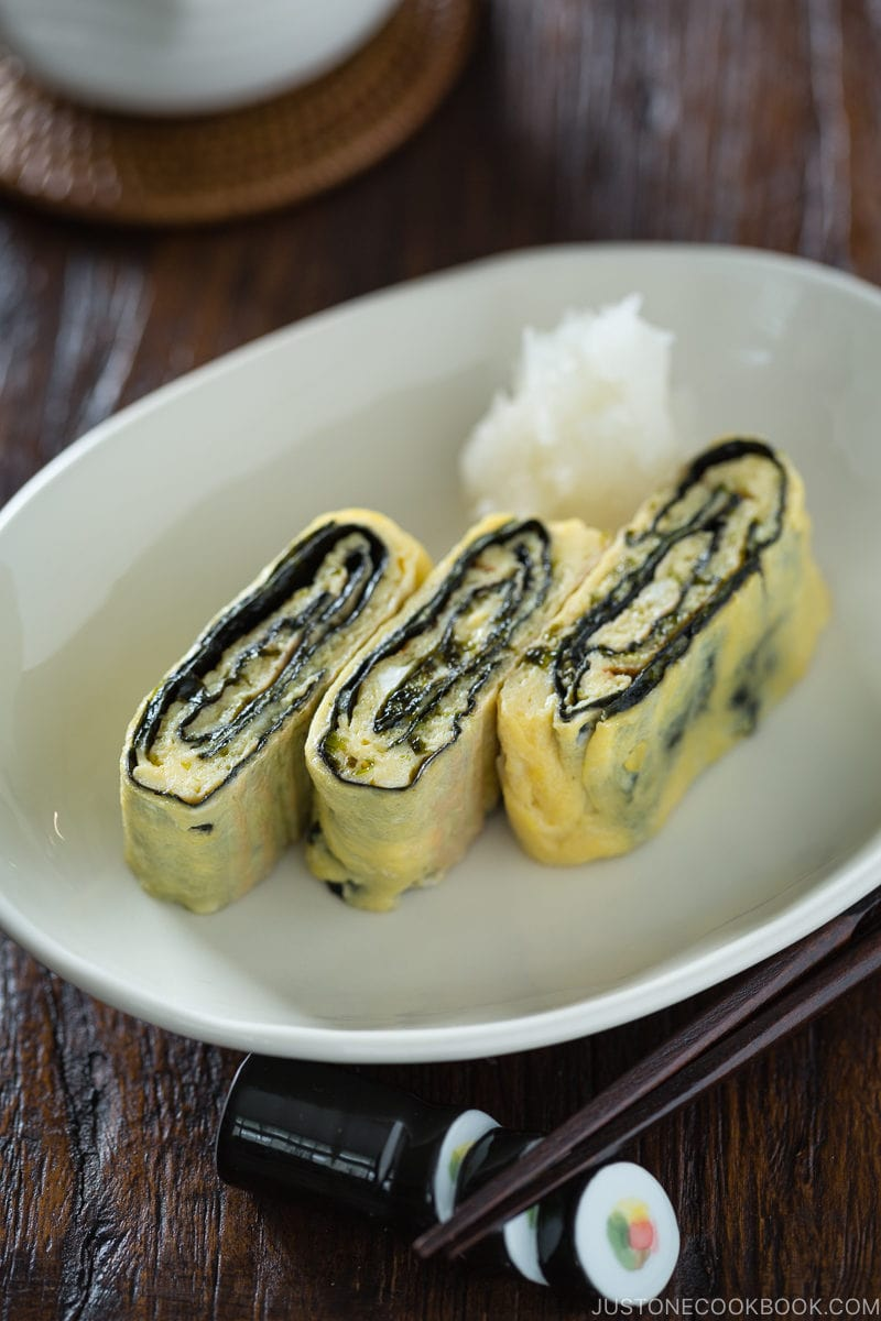 Tamagoyaki with nori seaweed in the middle served on a white plate.