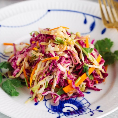 Asian Coleslaw with Sesame Dressing on a white plate along with gold fork and knife.