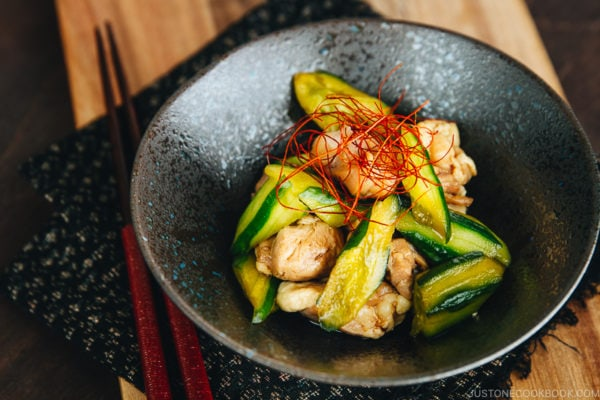 A black ceramic bowl containing Cucumber and Chicken Marinated in Chili Oil.