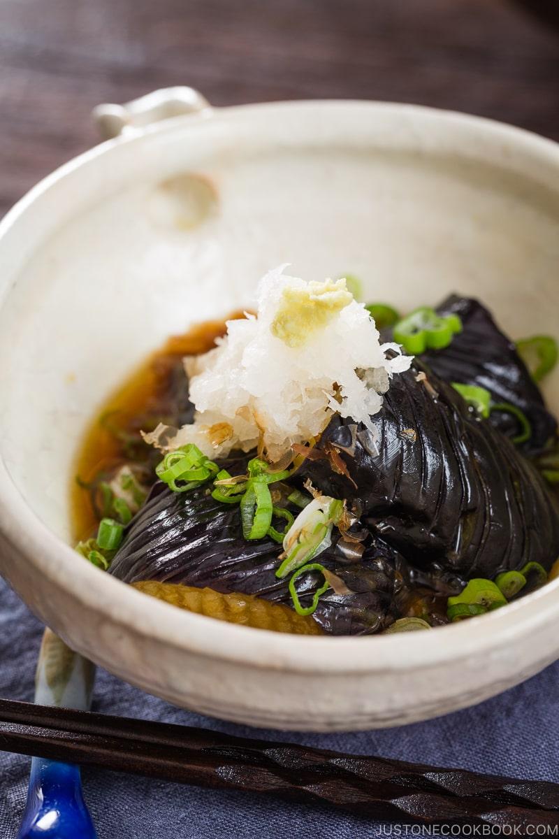 A white ceramic bowl containing eggplant agebitashi.