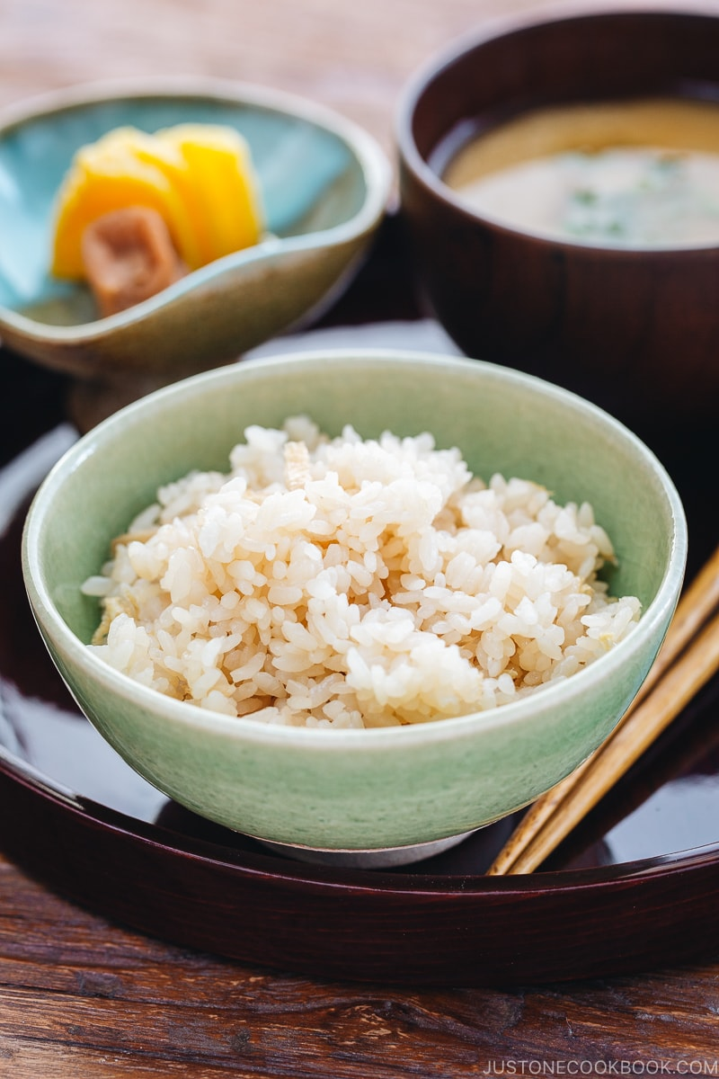 A rice bowl containing ginger rice which is served with miso soup and pickles.