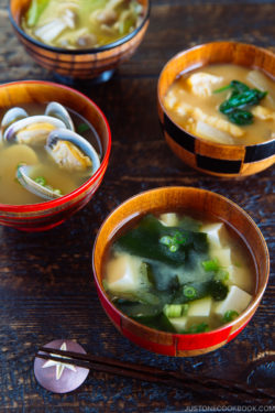 4 wooden miso soup bowls containing different types of miso soup.