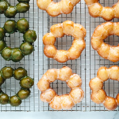 Homemade glazed and matcha glazed pon de ring donuts on a wire rack.