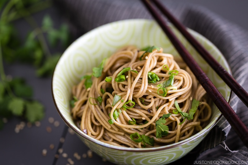 Soba noodle salad with soy honey dressing in a green bowl.