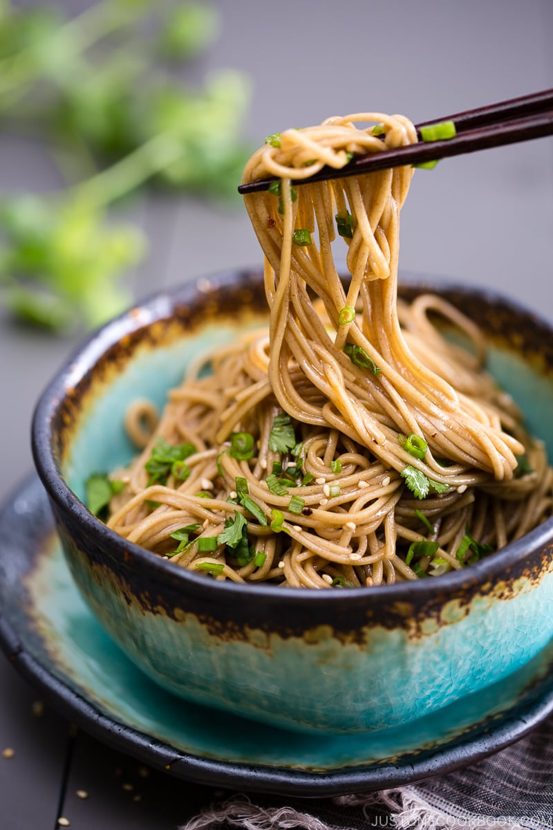 Soba noodle salad with soy honey dressing in a blue bowl.